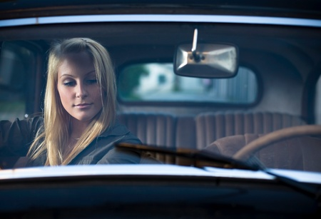 car inside: Portrait of a beautiful young blond in a vintage car, shot through the windscreen.