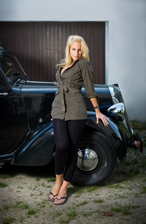 Beautiful young blond girl standing in front of a black vintage car. photo