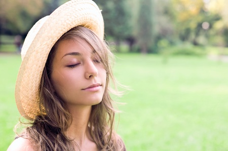 Beautiful relaxed young spring brunette enyjoying nature wearing a straw hat, eyes closed. Stock Photo - 9328639