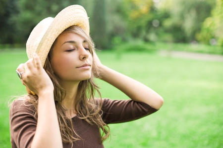 Beautiful relaxed young spring brunette enyjoying nature wearing a straw hat, eyes closed. photo