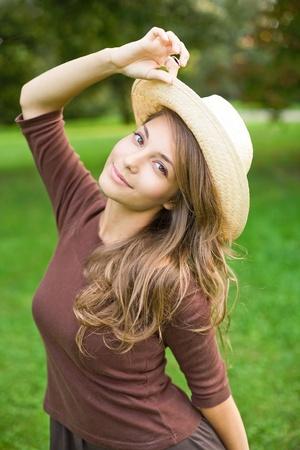 jolie jeune fille: Douce jeune brunette posant dans la nature, porter un chapeau de paille.