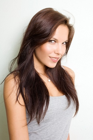 Hot young brunette in gray top smiling at the camera. Stock Photo - 9328748