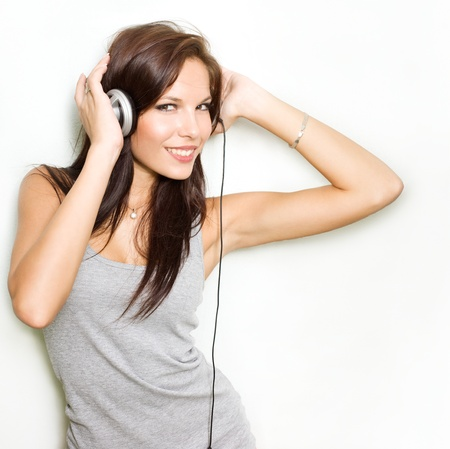 Hot dymanic young brunette listening to music in headhones.  Stock Photo - 9328779