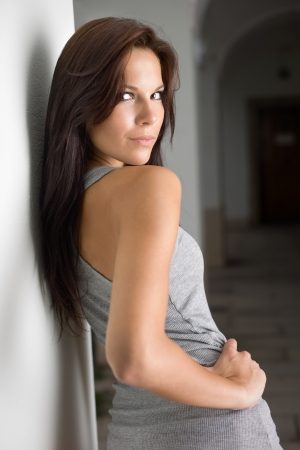 Portrait of a hot young brunette girl looking back over her shoulder.