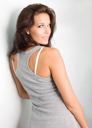 over the shoulders: Brunette hottie posing for the camera, looking back over her shoulder.