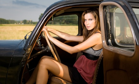 Gorgeous young bruinette posing outdoors with beautiful black vintage car. photo