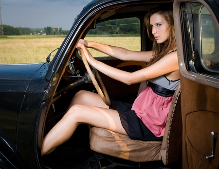 Gorgeous young brunette posing outdoors with beautiful black vintage car. photo
