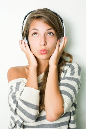 Beautiful young brunette listening to music with headphones.. photo