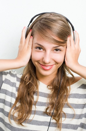 big smile: Beautiful young brunette listening to music with headphones, big smile.