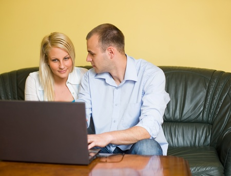 Portrait of attractive happy young couple using gray laptop at home. photo
