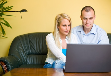 Attractive young couple using laptop sitting at home. photo