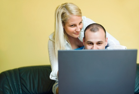 Attractive young couple having fun with laptop at home. photo