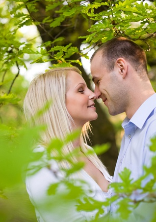 Romantic young couple holding each other in spring foliage. photo