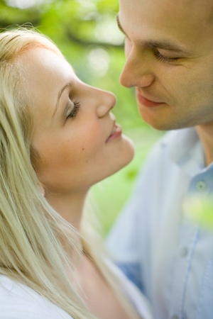 Attractive romantic young couple outdoors in nature, about to kiss. photo