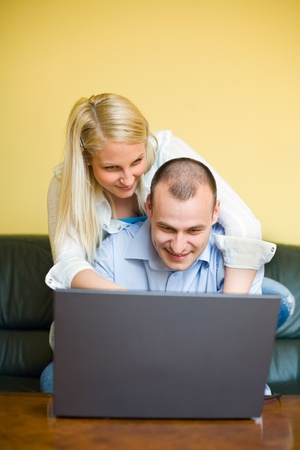 Young couple having fun with laptop at home. photo