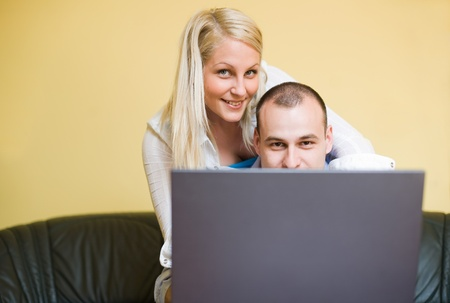 Young couple peeking over laptop screen at home. photo