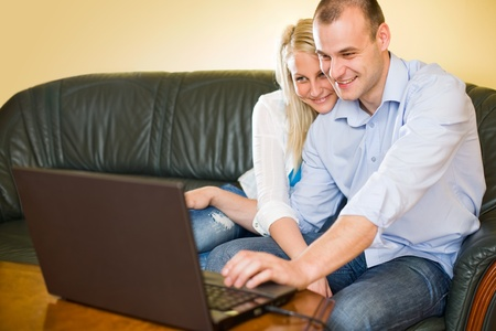 Attractive happy young couple having fun with laptop at home. photo