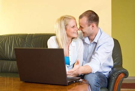 Attractive young couple happy about their findings using a laptop. photo