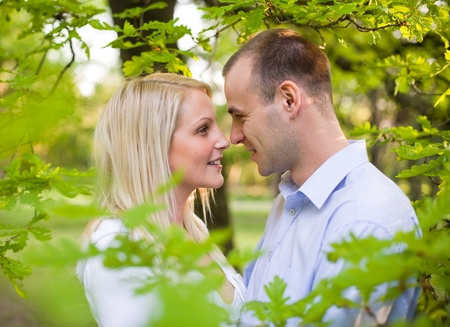 Romantic portrait of attractive young couple hiding in foliage. photo