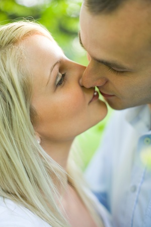 women kissing: Portrait of young couple sharing a romantic kiss. Stock Photo