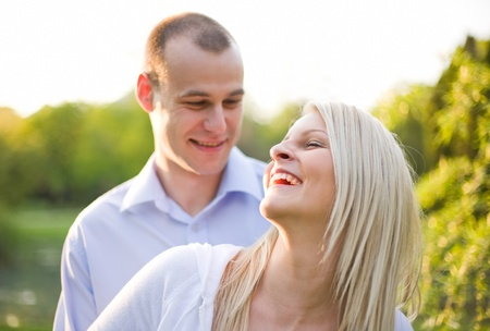 Fresh bright portrait of young couple outdoors at dusk. photo