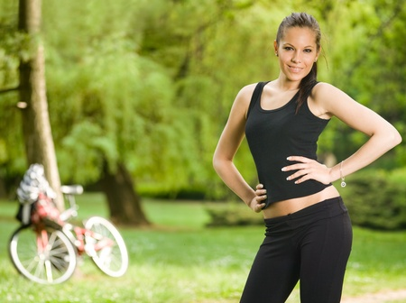skinny woman: Gorgeous young slim fitness brunette posing outdoors in nature. Stock Photo