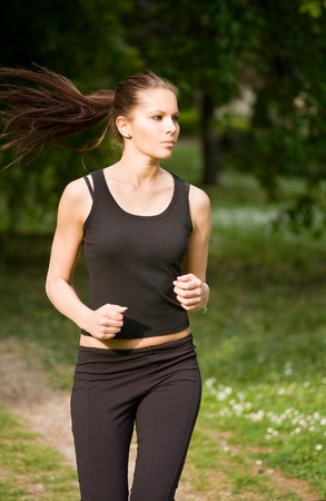 woman running: Beautiful fit slim brunette running outdoors in nature. Stock Photo