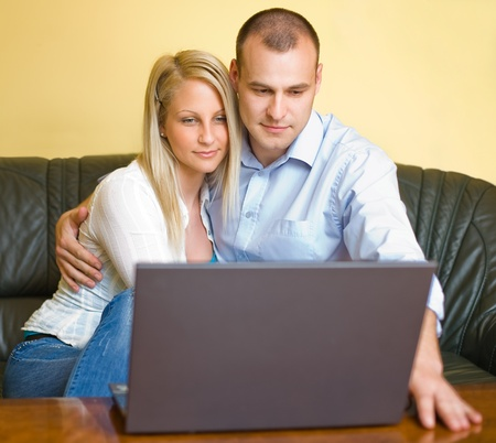 Attractive young couple using a laptop at home. photo
