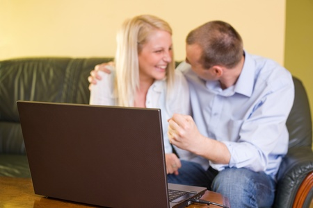 Attractive young couple happy about achievement using a laptop at home. photo