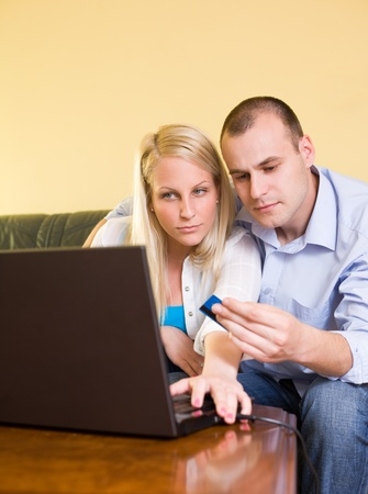 Young couple shopping online using credit card and a laptop at home. photo
