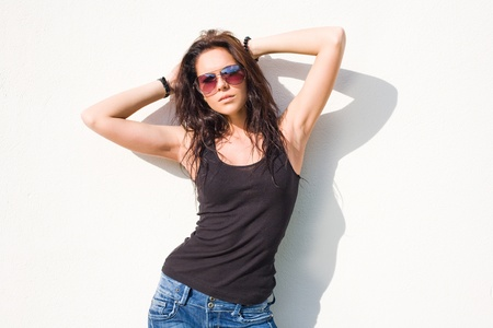 Hot young briunette girl in sunglasses enjoying sunshine. photo
