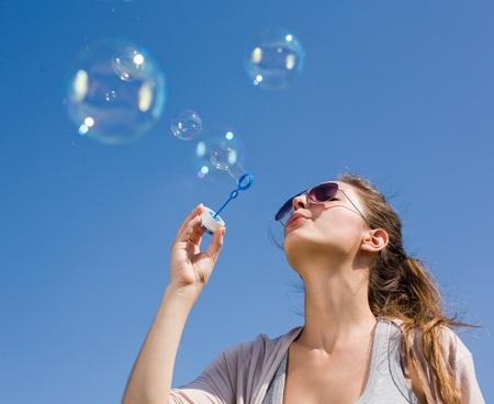 soap bubble: Gorgoeus young brunette blowing soap bubbles into the sky.
