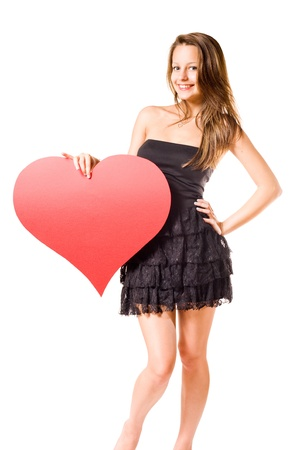 Gorgeous young brunette fooling around with large red heart shape, isolated on white background. photo