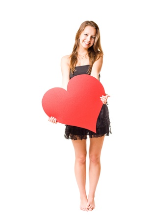 girl in red dress: Gorgeous young brunette fooling around with large red heart shape, isolated on white background. Stock Photo