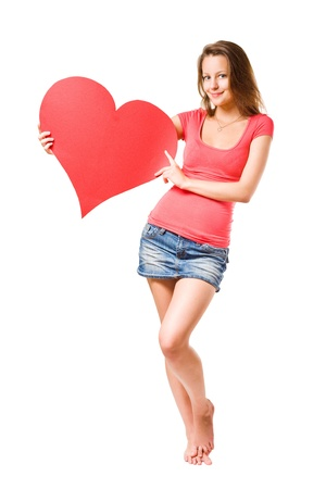 Beautiful casually dressed smiling happy young brunette girl holding large red heart shape, isolated on white background photo