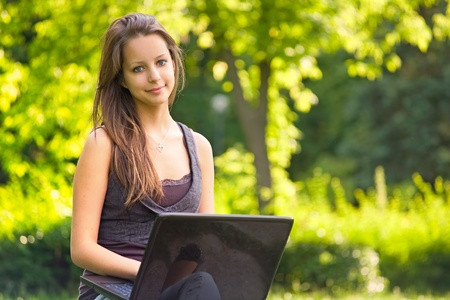 Beautiful young brunette teen using laptop outdoors in sunlit nature. Stock Photo - 9680632