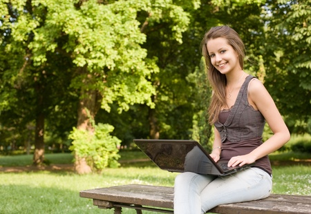 Beautiful young brunette teen using laptop outdoors in sunlit nature. photo