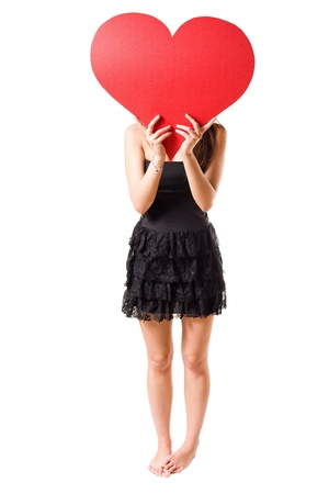 I love... beautiful young brunette girl holding big red heart, isolated on white background. photo
