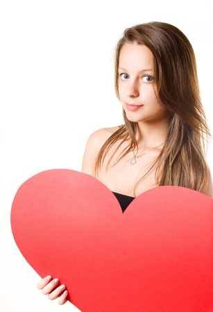 I love... beautiful young brunette girl holding big red heart, isolated on white background. Stock Photo - 9680665