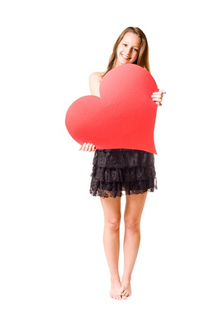 Gorgeous young brunette fooling around with large red heart shape, isolated on white background. Stock Photo