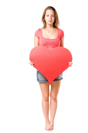 Beautiful young  brunette with slightly disillusioned expression holding large red paper heart sign, isolated on white background. photo