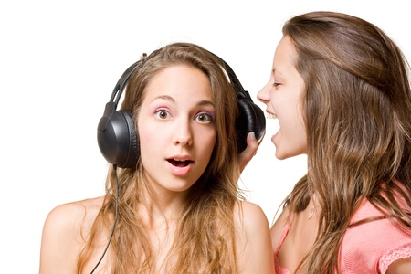 Share your music, two beautiful young brunette girls fighting oiver headphones, isolated on white background. Stock Photo - 9680711
