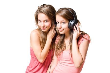 brunette teen: Teen radio, two gorgeous cute brunette teen girls having fun with headphones and music. Stock Photo