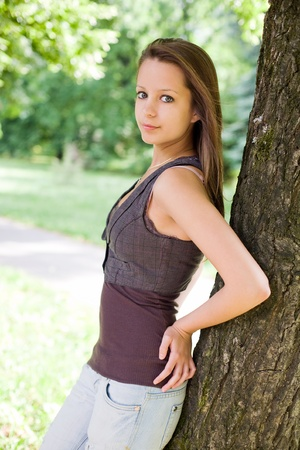 Beauitful slender young brunette girl posing outdoors at summer. Stock Photo - 9756172