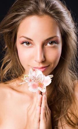 Beauty shot of smiling gorgeous brunette holding flower, on black background photo