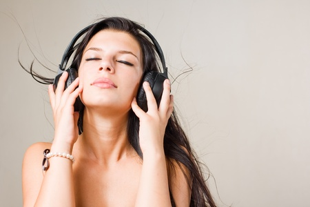 Gorgeous young brunette immersed in music wearing headphones, with eyes closed Stock Photo - 10160325