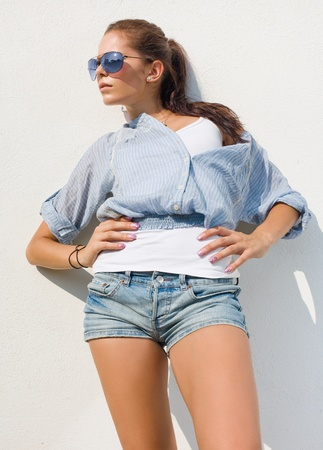 Casually dressed beautiful brunette in hot summer sunshine. photo