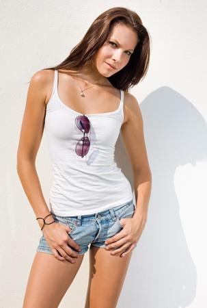 Beautiful young hot brunette posing in hot summer sunshine. Stock Photo - 10121367