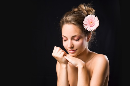 beauty shot: Beauty shot of gorgeous young brunette girl with tranquil expression and flower, eyes closed.