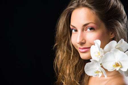 Gorgeous brunette closeup beauty shot with white orchid. photo